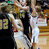 FVMON09<br /> Monarch's Alex Evans gets up a shot while pressured from Casey Thayer, left, and Kristen Narum of Fairview. <br /> Photo by Marty Caivano/Camera/Jan. 19, 2010