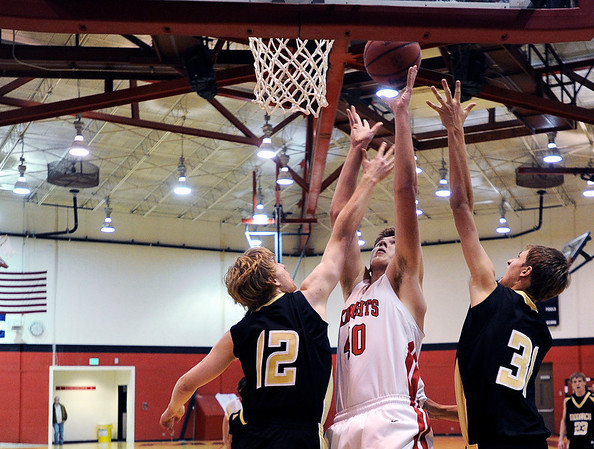 "Fairview's Enrique Busatta takes a shot over Monarch's Dan Sorenson, left, and Ben Beauchamp during a basketball game against Monarch High School on Wednesday, Dec. 7 at Fairview. Fairview won the game 50-26. For more photos of the game go to  <a href=""http://www.dailycamera.com"">http://www.dailycamera.com</a><br /> Jeremy Papasso/ Camera"