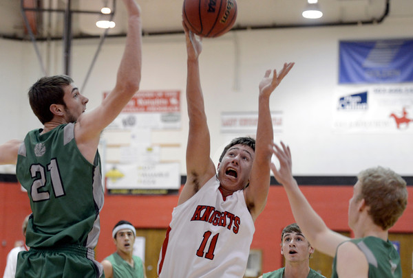 """Fairview High School's Cubby Lane takes a shot under the arms of Clarke Colwell during a game against Niwot High School on Monday, Dec. 10, at Fairview High School in Boulder. For more photos of the game go to  <a href=""""http://www.dailycamera.com"""">http://www.dailycamera.com</a><br /> Jeremy Papasso/ Camera"""