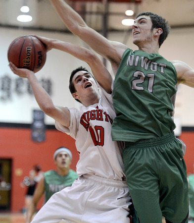 """Fairview High School's Trevor McQuenney takes a shot under the guard of Clarke Colwell during a game against Niwot High School on Monday, Dec. 10, at Fairview High School in Boulder. For more photos of the game go to  <a href=""""http://www.dailycamera.com"""">http://www.dailycamera.com</a><br /> Jeremy Papasso/ Camera"""