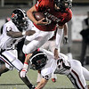 Fairview High School quarterback Michael McVenes tries to jump over Pomona junior Zach Perez, right, while rushing the ball on Friday, Oct. 15, during a football game at Recht Field in Boulder. <br /> Jeremy Papasso/ Camera