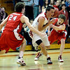 Fairview's Shane O'Neill (middle) power past Regis' Bud Thomas (left) and Colin Smith (right) during their basketball game in the Fairview Festival in Boulder, Colorado December 11, 2009.  CAMERA/Mark Leffingwell