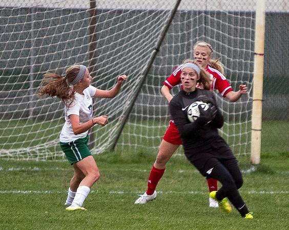 SAM HOUSEHOLDER | THE GOSHEN NEWS<br /> Goshen keeper junior Alyssa Hershberger saves a ball between Concord junior Emma Paden and Goshen freshman Jillian Kissinger during the game Tuesday.