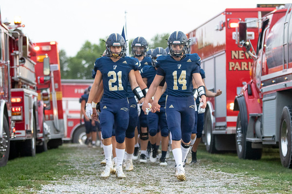 Fairfield Falcons defensive back Quinn Kitson (21) and quarterback Cory Lantz (14) lead their team onto the field Friday before the game through the tunnel formed by the New Paris Fire Department in honor of senior night at Fairfield Jr.-Sr. High School.