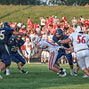 Goshen senior Roman Schrock tries to run the ball while being held back by a Falcon defender during the first half of the teams' game Friday night in Benton.