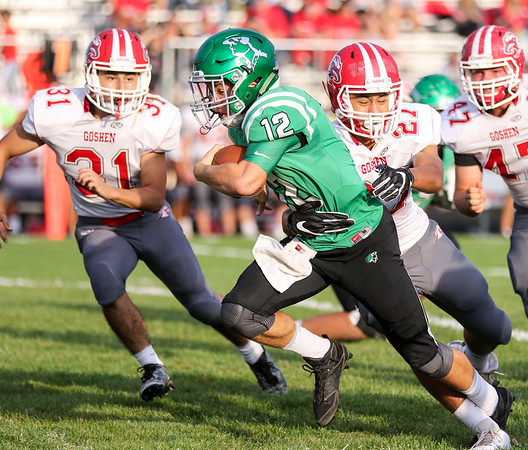 CHAD WEAVER | THE GOSHEN NEWS<br /> Concord quarterback Jack Lietzan rushes the ball up the middle while Goshen safety Brandon Holley tries to bring him down during the first quarter of Friday night's game at Concord. Behind them is Goshen linebacker Liam Morales.