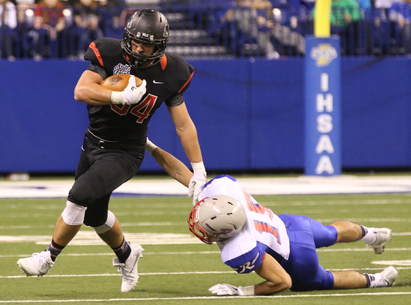 JAY YOUNG | THE GOSHEN NEWS <br /> NorthWood junior Payton Bear (34) slips a tackle attempt by Indianapolis Roncalli's Gabe Otley (15) during the 4A state championship game Friday afternoon at Lucas Oil Stadium in Indianapolis.