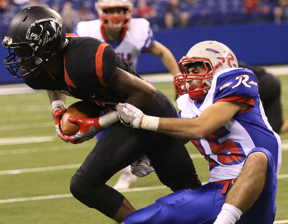JAY YOUNG | THE GOSHEN NEWS <br /> Northwood junior DeAndre Smart catches a pass but is quickly brought down by Roncalli senior Gabe Otley (15) during the first half of the class 4A state championship game Friday afternoon at Lucas Oil Stadium in Indianapolis.