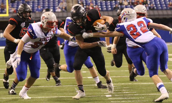 JAY YOUNG | THE GOSHEN NEWS <br /> Northwood sophomore Bronson Yoder, center, slices through the Roncalli defenders John Harris, left, and Dylan Williams (22) during the first half of the class 4A state championship game Friday afternoon at Lucas Oil Stadium in Indianapolis.