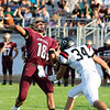 CHAD WEAVER | THE GOSHEN NEWS<br /> Jimtown quarterback Sam Pawlak launches a deep pass while being pressured by NorthWood linebacker Payton Bear during the first quarter of Friday night's game at Jimtown.