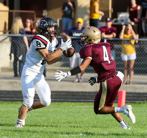 CHAD WEAVER | THE GOSHEN NEWS<br /> NorthWood wide receiver Landen Gessinger catches his first of two first-quarter touchdown receptions Friday night at Jimtown. Defending for Jimtown is senior Sevon Gillespie.