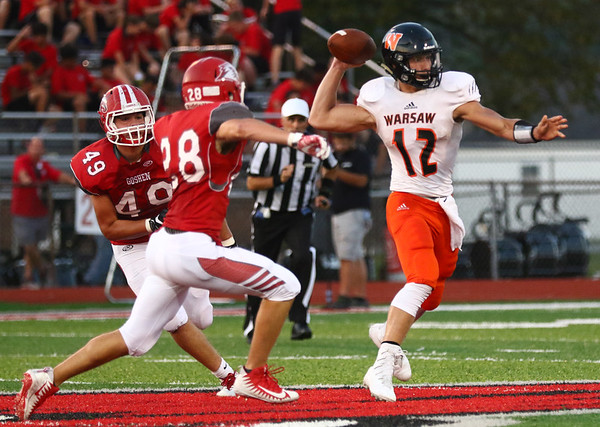 JAY YOUNG | THE GOSHEN NEWS<br /> Warsaw High School quarterback Tristan Larsh (12) looks to get rid of the ball as he is pressured in the backfield by Goshen High School defenders Joseph Burkheimer (28) and Will Koshmider (49) during their game Friday night at GHS.