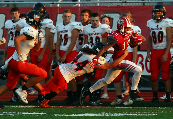 JAY YOUNG   THE GOSHEN NEWS<br /> Goshen High School senior Dominick Swinney (19) races down the sidelines as he tried to escape from Warsaw High School senior Lane McClone (44) after making a reception during their game Friday night at GHS.