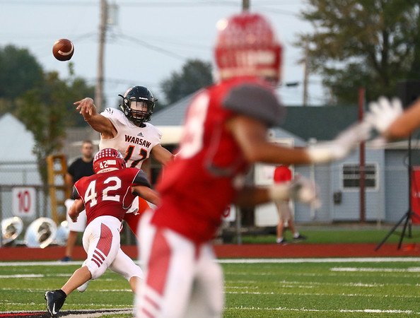 JAY YOUNG | THE GOSHEN NEWS<br /> Warsaw High School quarterback Tristan Larsh (12) lets the ball fly downfield as he is hit by Goshen High School linebacker Ian Hostetler (42) during their game Friday night at GHS.