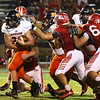 JAY YOUNG | THE GOSHEN NEWS<br /> Warsaw High School running back Bryce Garner (28) slips through the Goshen High School defensive line  during their game Friday night at GHS.