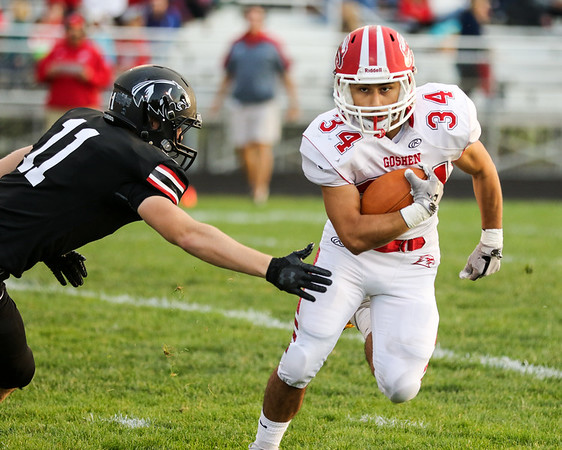 CHAD WEAVER   THE GOSHEN NEWS<br /> Goshen running back Liam Morales tries to avoid NorthWood linebacker Jake Lone after taking a handoff during the first quarter of Friday night's game at NorthWood.