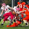 SAM HOUSEHOLDER | THE GOSHEN NEWS<br /> Goshen running back sophomore Jeff Stoll is tackled by two Warsaw Tiger defenders Friday during the game.