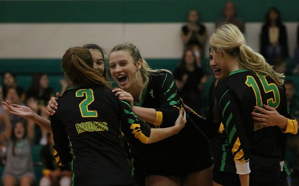 Northridge senior Abby Martin, center, celebrates with senior Ashley Penzenik (2) and the rest of her teammates after scoring a point during Tuesday's match against Lakeland at Northridge High School in Middlebury.