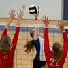 SAM HOUSEHOLDER | THE GOSHEN NEWS<br /> Bethany senior Erin Bontrager hits a ball over the net while Westview defenders Miranda Kresse (5) and Maria McCoy (22), both juniors, try to block.