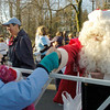 Andover: At left, Grace Alwan, 8, of Andover, receives a candy cane from a runner dress as santa near the starting line of the 21st Annual Feaster Five Road Race in Andover Thanksgiving morning. Photo by Tim Jean/Eagle-Tribune Thursday, November 27, 2008
