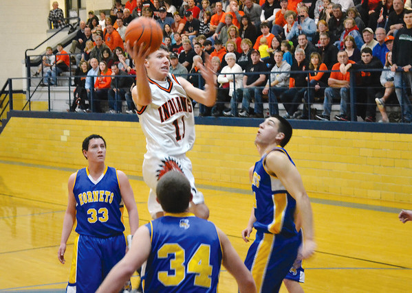 Altamont's Justin McGinnis skies for a layup between Cowden-Herrick's Ethan Schoonover (33), Tyson Morgason (34) and Luke Moore (right) night in St. Elmo.