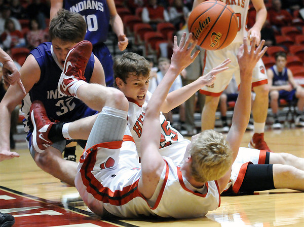 Effingham's Kennan Mahaffey (front) and Jake Stombaugh (back) dive for a loose ball with an unknown defender from Mascoutah in Centralia.