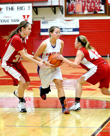 Vandalia's Madeline Hosick (left) and Karlie Bright (right) attempt to strip the ball from Newton's Emily Kerner.