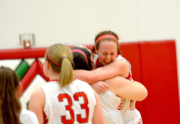 Effingham's Josie Zerrusen smiles while being embraced and spun by teammate Maddy Field after the Lady Hearts bested Salem 43-30 to win the Class 3A Effingham Regional title.