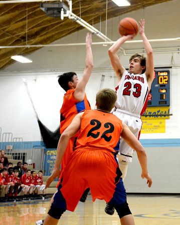 Neoga's Wyatt Krikie rises up for a jumper over a pair of Palestine/Hutsonville defenders.