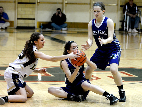 Teutopolis' Cierra Thompson attempts to steal the ball from Breese Central's Torre Kohrmann while both are on the ground, as Sophie Rickhoff (right) looks on and tries to receive a hand off at the Salem Super-Sectional.