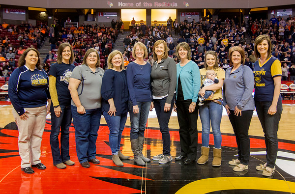 The 1986 Teutopolis Lady Shoes were honored at halftime of the Class 2A third-place game for the 30th anniversary of their state championship, just minutes before Teutopolis played for the Class 2A state championship. From left: current Teutopolis coach Laurie (Holman) Thompson, Beth (Niebrugge) Hartke, Cindy (Westendorf) Funneman, Lisa Schumacher, Angie (Ruholl) Jansen, Sandy (Braun) Michels, Doris (Carie) Zerrusen, Avyree Scholes holding Andrew Koester, Gina (Beckman) Zerrusen, and Connie (Ruholl) SchultzLaurie (Holman) Thompson, Beth (Niebrugge) Hartke, Cindy (Westendorf) Funneman, Lisa Schumacher, Angie (Ruholl) Jansen, Sandy (Braun) Michels, Doris (Carie) Zerrusen, Avyree Scholes holding Andrew Koester, Gina (Beckman) Zerrusen, Connie (Ruholl) Schultz.