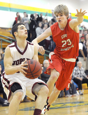 Joplin's JAce Braker looks for a shot as Carl Junction's Braydon Allen closes in on defense during their game on Tuesday night at Robert Ellis Young Gymnasium.<br /> Globe   Laurie Sisk