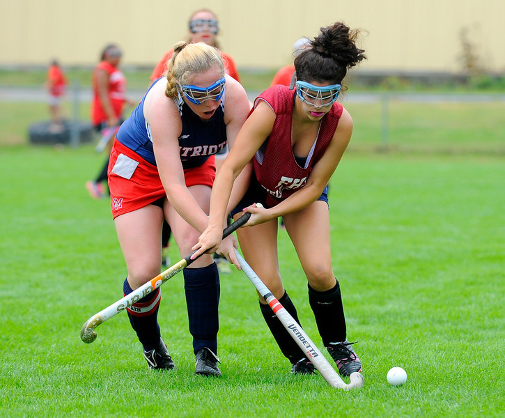 North Middlesex' Kylene O'Neil (left) and Fitchburg's Sam Benoit battle for possession of the ball during Saturday's Field Hockey Play Day at St. Bernard's in Fitchburg.<br /> SENTINEL & ENTERPRISE / BRETT CRAWFORD