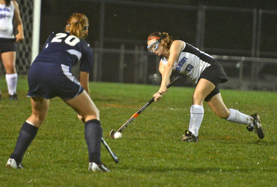 Midd West's Danielle Ulrich (20) faces off against Mifflinburg's Jackie Beck (20) during the field hockey game on Thursday night in Middleburg. Mifflinburg won 1-0.