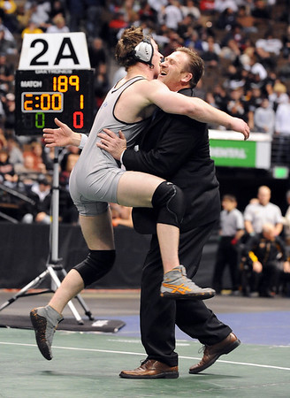 Josh Van Tine jumps in the arms of his father Mark after winning the 171-pound, 4A state championship match, which also clinched state for Broomfield.<br /> Cliff Grassmick / February 20, 2010