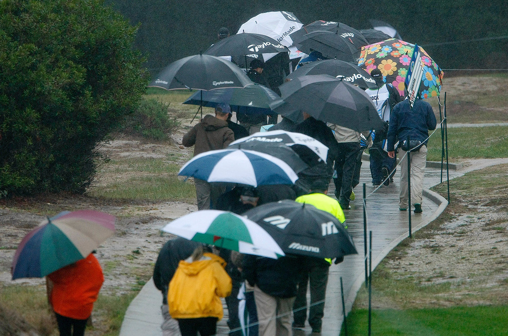 . The gallery leaves the course after a rain delay at Spyglass Hill Golf Course during the first round of the AT&T Pebble Beach National Pro Am on Feb. 6, 2014.  (Vern Fisher/Monterey County Herald)