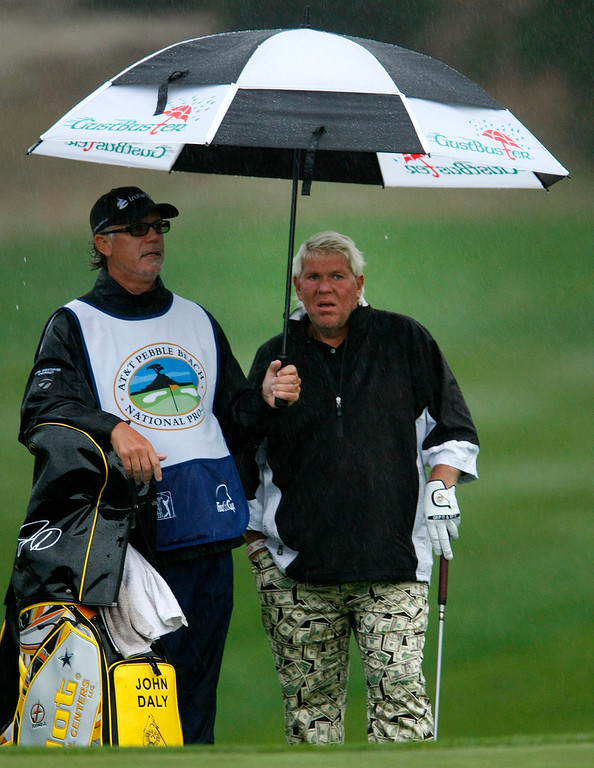 . John Daly takes cover from the rain at Spyglass Hill during the first round of the AT&T Pebble Beach National Pro Am on Feb. 6, 2014.  (Vern Fisher/Monterey County Herald)
