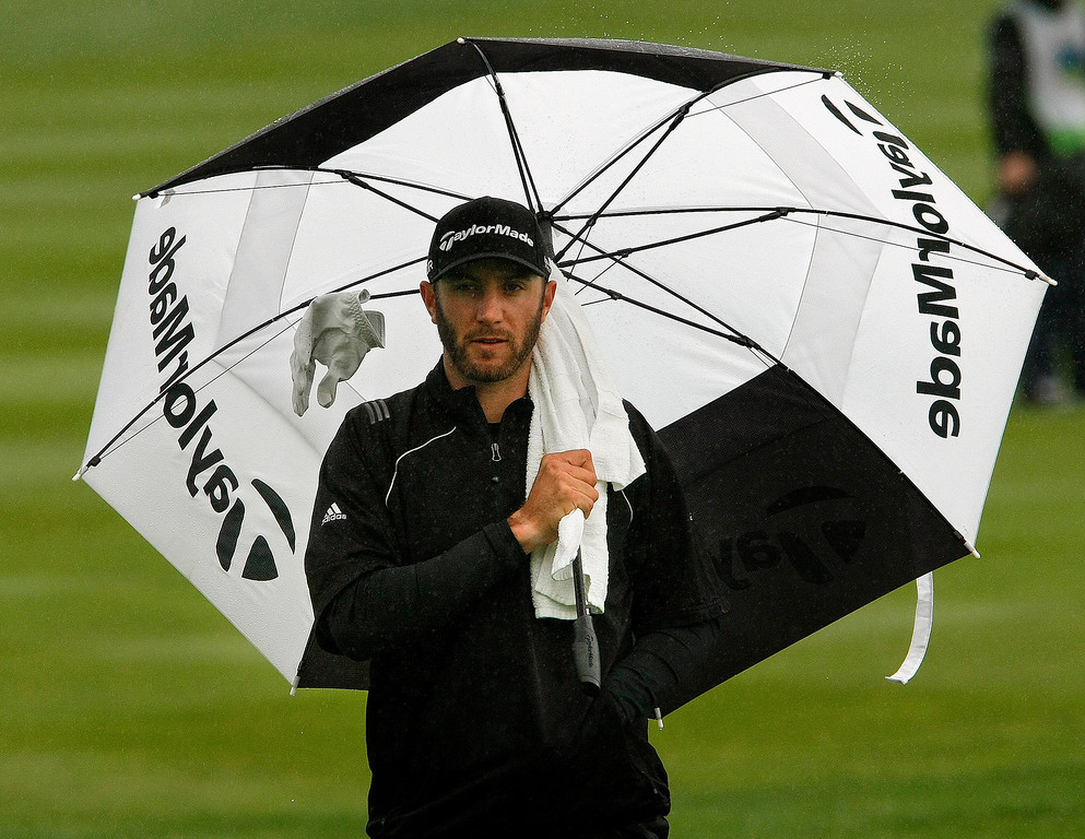 . Dustin Johnson takes cover from the rain at Spyglass Hill Golf Course during the first round of the AT&T Pebble Beach National Pro Am on Feb. 6, 2014.  (Vern Fisher/Monterey County Herald)