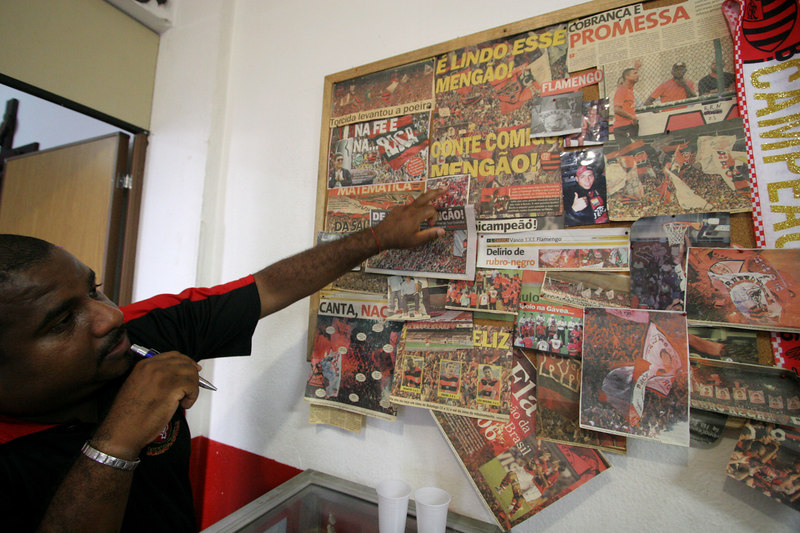 Flamengo fan club member and fan leader Junior looks at newspaper clippings  at the club office in Rio de Janeiro, Brazil, March 16, 2006. The fan club has profited from the team's recent sucesses. More members are joining and buying merchandise ever since last year's Copa do Brasil championship earned the team a spot in this year's Libertadores Cup (South America's version of the Champion's League) after a five-year absence.