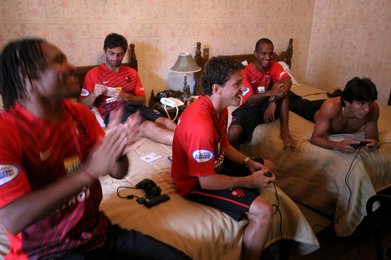 Members of Brazil's Flamengo team  Claiton, far left, and Juninho Paulista, center, play video game football at the team's hotel in Sucre, Bolivia, Feb. 14, 2007, before a Libertadores Cup match against Real Potosi, high in the Bolivian Andes. Flamengo, Brazil's most popular club, is back in the Libertadores Cup (South America's version of the Champion's League) after a five-year absence. Real Potos', bought by a Real Madrid fan several years ago and who's emblem is remarkably similar to their Spanish counterpart, is in the tournament for the second time. Flamengo's trip to one of the world's highest professional soccer venues for the group 5 match against Potos' has proved a logistical nightmare for Flamengo because of the difficulties of playing at nearly 4,000 metres above sea level as well as the task of simply reaching the match venue. Potosi does not have a commercial airport and Flamengo flew to Sucre then made a three-hour bus journey up precipitous mountain roads to get there. Flamengo players were given bursts of oxygen during and after the match, which they managed to draw 2-2. Flamengo goals were scored in the 49th minute by Roni, who headed a free kick from the left, and Obina on an identical play in the 67th minute. After the match Flamengo leadership said that they will not play at that altitude again, prompting a controversy with the Bolivians, who say that they may refuse to play in Rio's 40 degree heat and humidity. Venezuela's Union AtlŽtico Maracaibo and Brazil's Paran‡ are also in group 5.