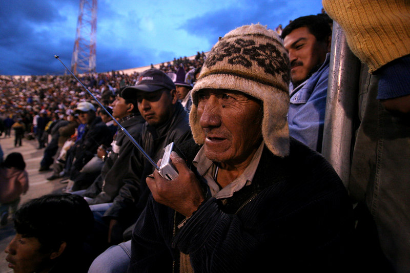 A Real Potosi fan listens to a broadcast of a Libertadores Cup match against Brazil's Flamengo in the sold-out 17,000 capacity Mario Mercado stadium before in Potos', a Spanish-colonial silver mining town high in the Bolivian Andes, Feb. 14, 2007. Flamengo, Brazil's most popular club, is back in the Libertadores Cup (South America's version of the Champion's League) after a five-year absence. Real Potos', bought by a Real Madrid fan several years ago and who's emblem is remarkably similar to their Spanish counterpart, is in the tournament for the second time. Flamengo's trip to one of the world's highest professional soccer venues for the group 5 match against Potos' has proved a logistical nightmare for Flamengo because of the difficulties of playing at nearly 4,000 metres above sea level as well as the task of simply reaching the match venue. Potosi does not have a commercial airport and Flamengo flew to Sucre then made a three-hour bus journey up precipitous mountain roads to get there. Flamengo players were given bursts of oxygen during and after the match, which they managed to draw 2-2. Flamengo goals were scored in the 49th minute by Roni, who headed a free kick from the left, and Obina on an identical play in the 67th minute. After the match Flamengo leadership said that they will not play at that altitude again, prompting a controversy with the Bolivians, who say that they may refuse to play in Rio's 40 degree heat and humidity. Venezuela's Union AtlŽtico Maracaibo and Brazil's Paran‡ are also in group 5.