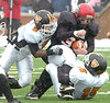 J.I. Burton defenders Malik Miles, #5, and Bradly Skeens, #15, tackle Holston ball carrier, #30 (I think) at the line for no gain. Photo by Ned Jilton II