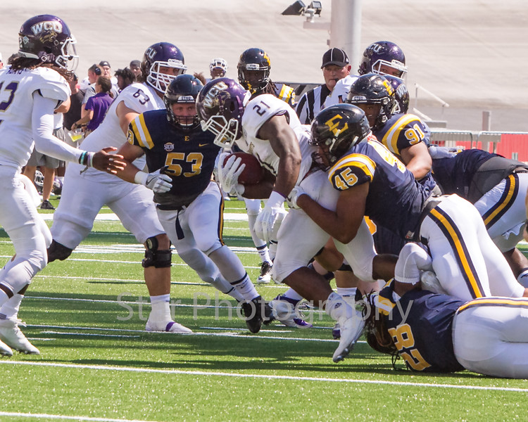 Star Photo/Larry N. Souders<br /> Catamount running back Detrez Newsome (21) is tackled for a loss by Marion Watson (46) and a swarming Buccaneers defense.