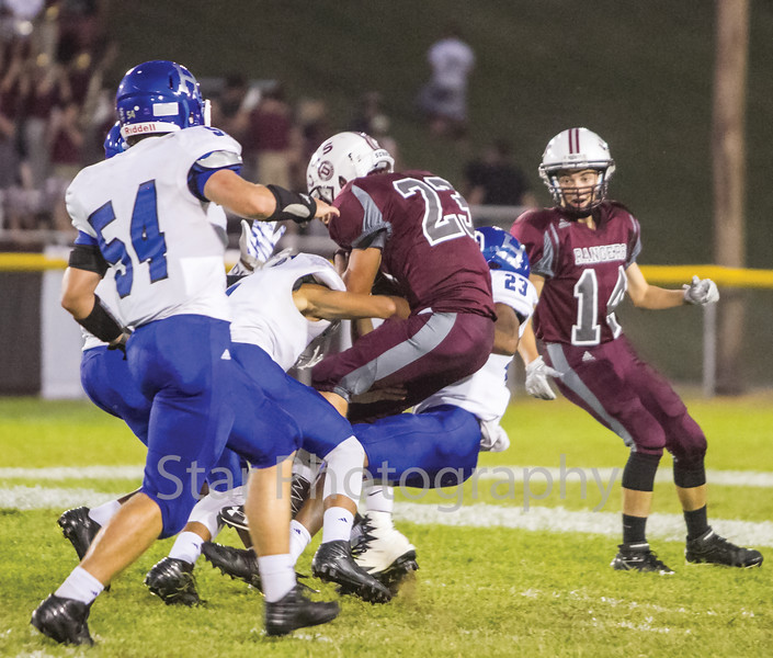 Star Photo/Larry N. Souders<br /> Rangers' tailback Ray Combs (20) runs for a first down before being tackled by a swarm of Blue Devils of Harriman in the first quarter of Friday night's game at Unaka.