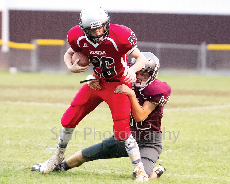 Star Photo/Larry N. Souders<br /> A Ranger defender (42) drags the Rebels running back (26) down from behind preventing a first down.