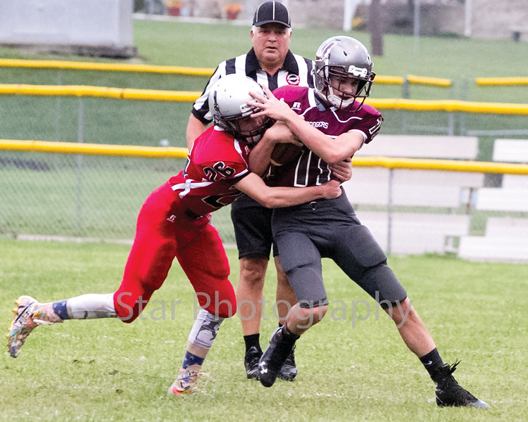Star Photo/Larry N. Souders<br /> A Ranger's wide receiver (17) tries to push off a tackle by a Rebel defender (26) from Cane River Middle School.