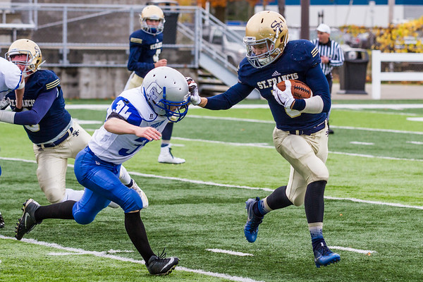 Record-Eagle/Brett A. Sommers Traverse City St. Francis' Teddy Prichard stiff arms Calumet tackler Samuel Erkkila during Saturday's pre-district playoff football. St. Francis won 28-6.