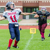 Record-Eagle/Brett A. Sommers Big Rapids Crossroads quarterback Justin Gernsey throws as he is chased from the pocket by Grand Traverse Academy's Hunter Bancroft (71) during Saturday's game. GTA won 48-10.