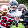 Record-Eagle/Brett A. Sommers Big Rapids Crossroads running back Tyler Dennis tries to escape the grasp of Grand Traverse Academy's Emerson Schlegel during Saturday's game. GTA won 48-10.