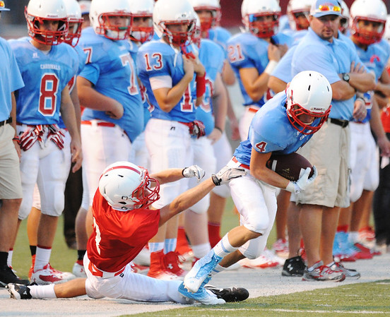Globe/T. Rob Brown<br /> Seneca's Ethan Dorland attempts to pull Webb City wide receiver Trent Parra out of bounds but is unsuccessful during Friday evening's jamboree, Aug. 23, 2013, at Webb City's field.